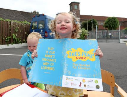 A child showing the logo of Let's Play Cork