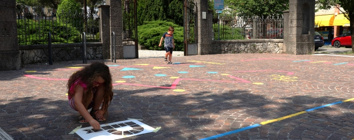 Children drawing they're own games on a city's pavement